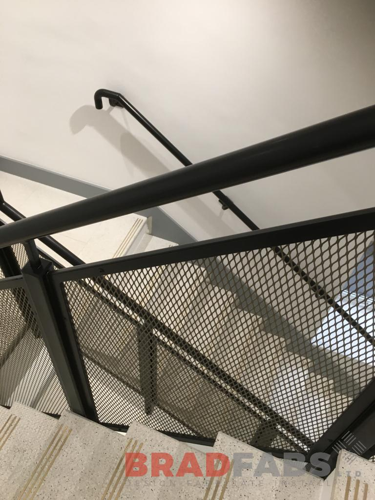 Mild steel and powder coated mesh panel balustrade to commercial staircase by Bradfabs Ltd