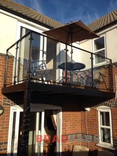 Balcony with two support legs, perfect for sitting out on a summers evening! Manufactured in mild steel, galvanised and powder coated black, with glass infill panels and composite decked flooring by Bradfabs