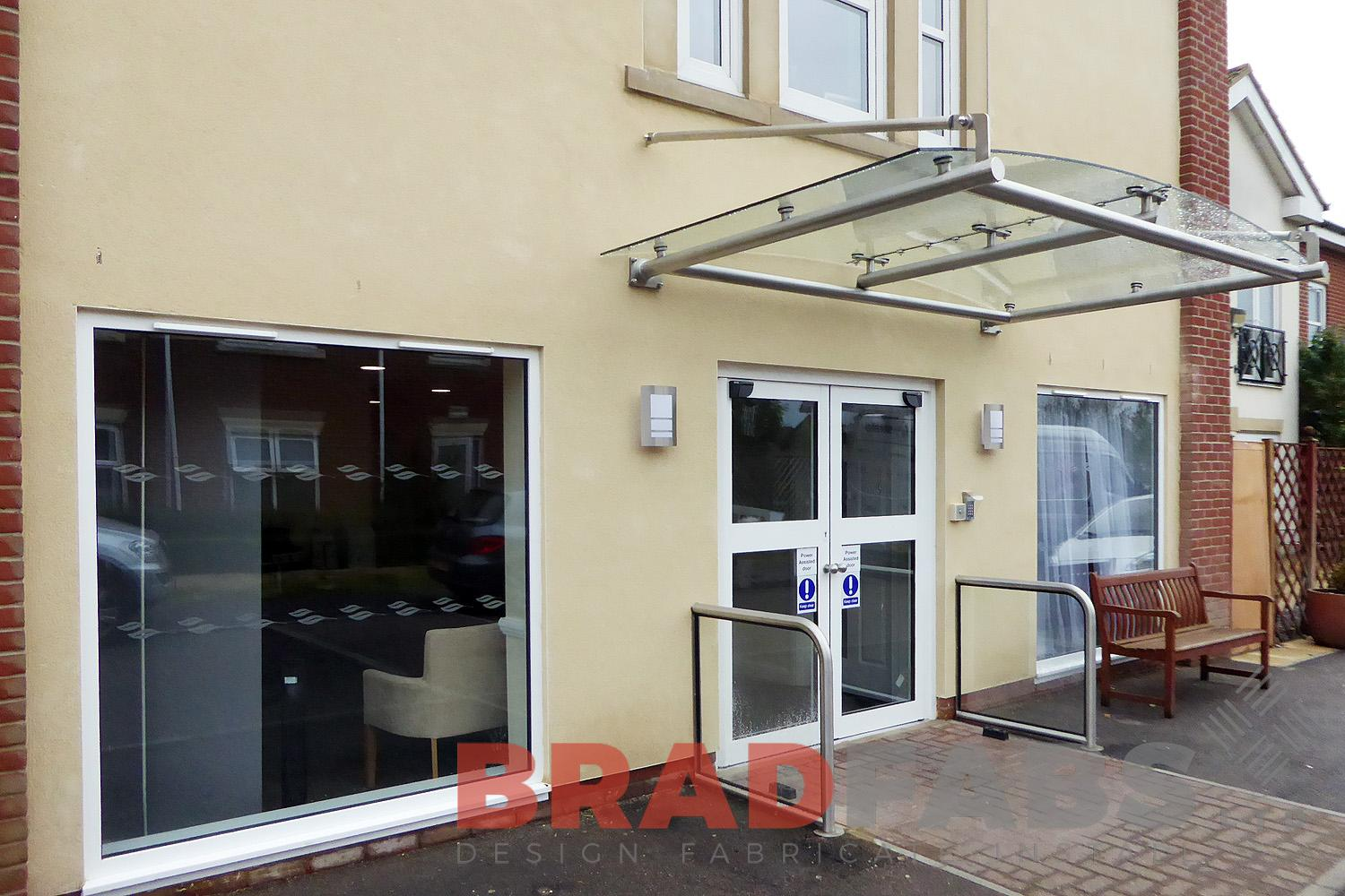 large curved glass and steel panel canopy in an entrance installed in nursing home