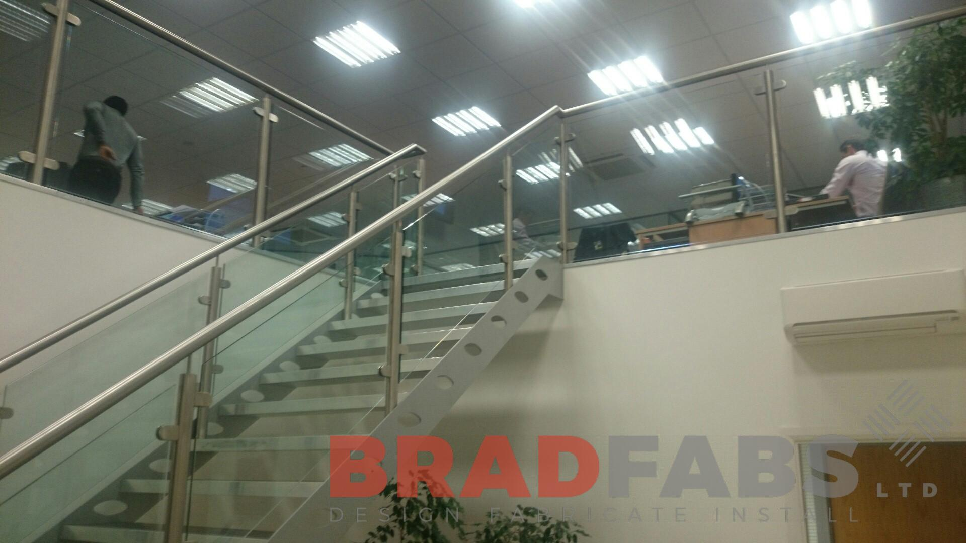Large modern straight staircase open treads stainless steel balustrade glass infil panels