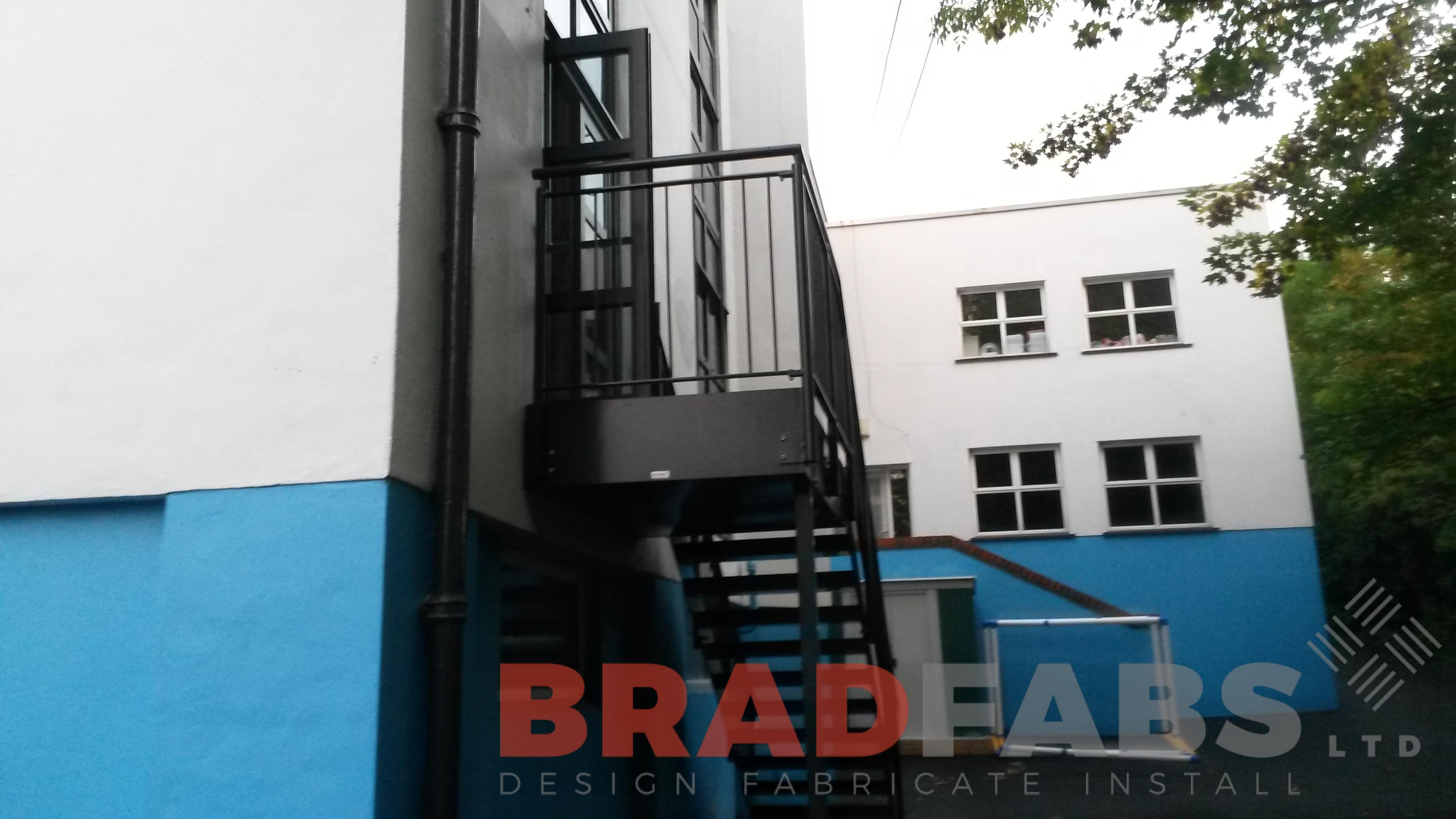 Straight fire escape mild steel powder coated black and galvanised with vertical bar balustrde and durbar treads by Bradfabs Ltd UK