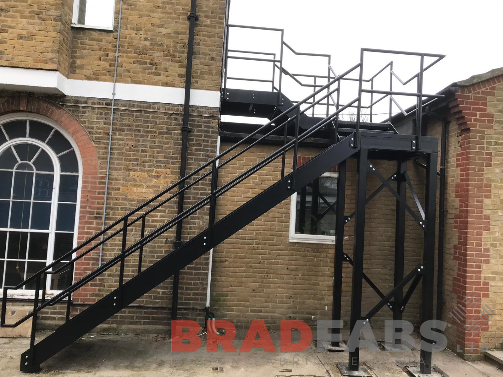 External straight staircase manufactured in mild steel, galvanised and powder coated in black with mid and top rail balustrade and durbar treads by Bradfabs