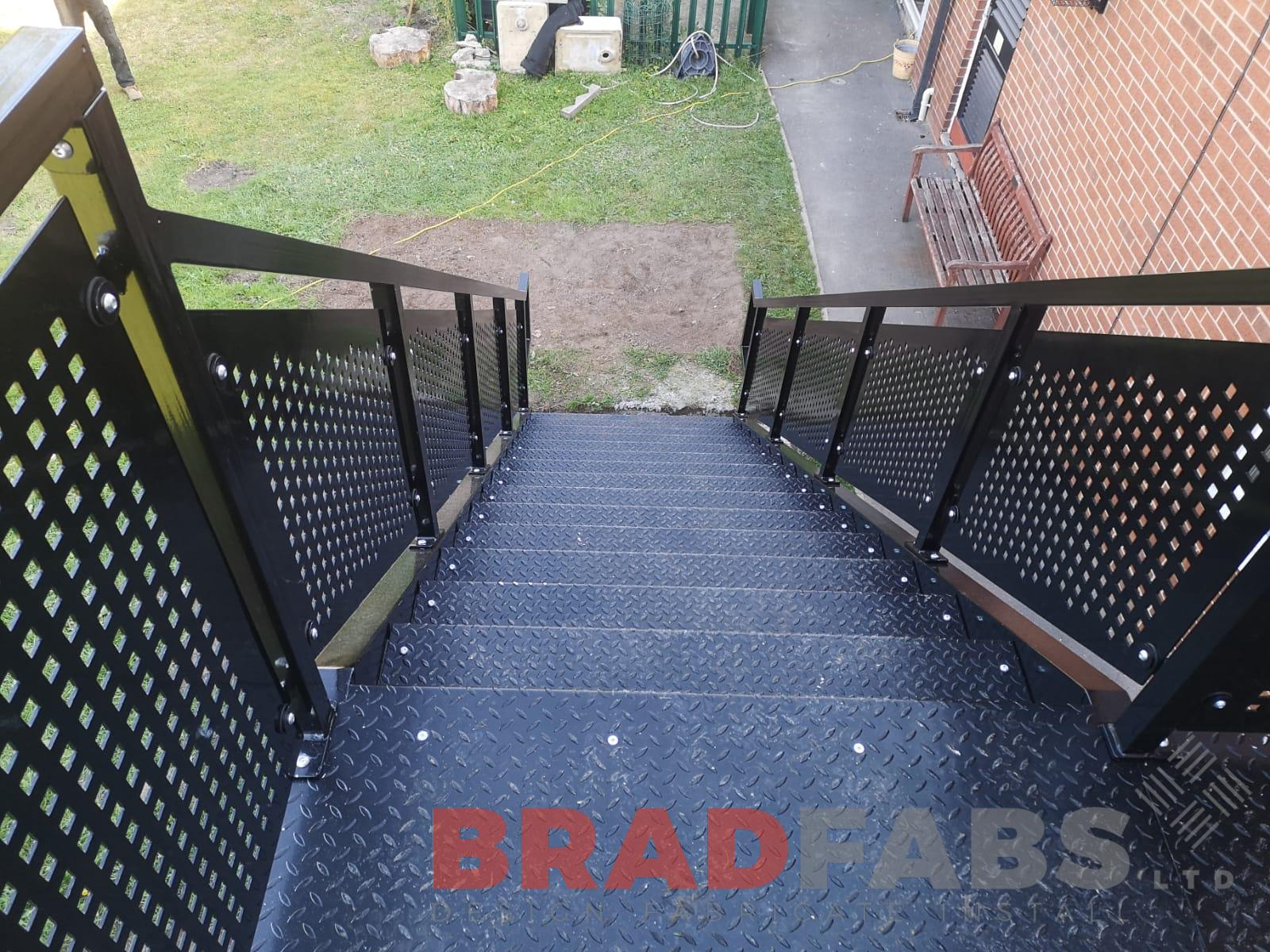 Vioew from the top of the straight fire escape manufactured in mild steel, galvanised and powder coated black with perforated balustrade and compete with durbar open treads by Bradfabs