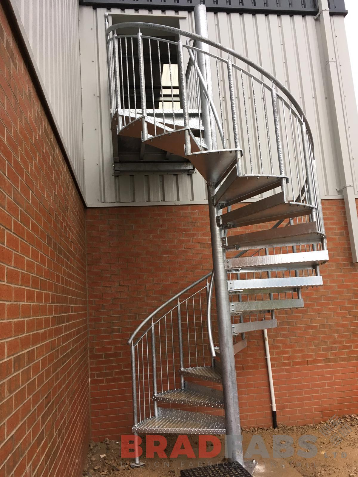 Mild steel and galvanised bespoke spiral fire escape with vertical bar balustrade and durbar treads, complete with a landing at the top by Bradfabs