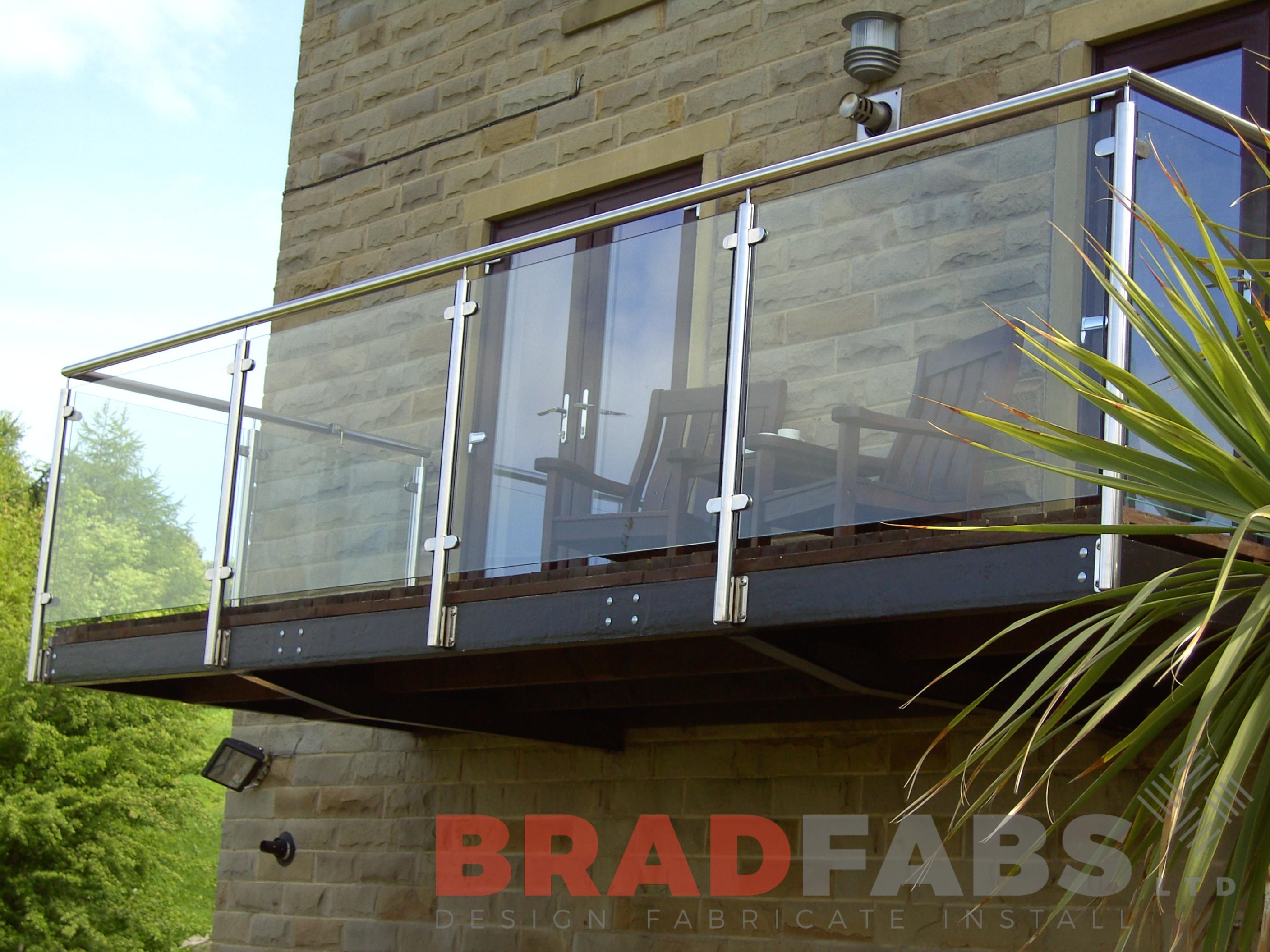 Large balcony at a domestic property. Stainless steel balustrade with glass infill panels and composite decked flooring by Bradfabs