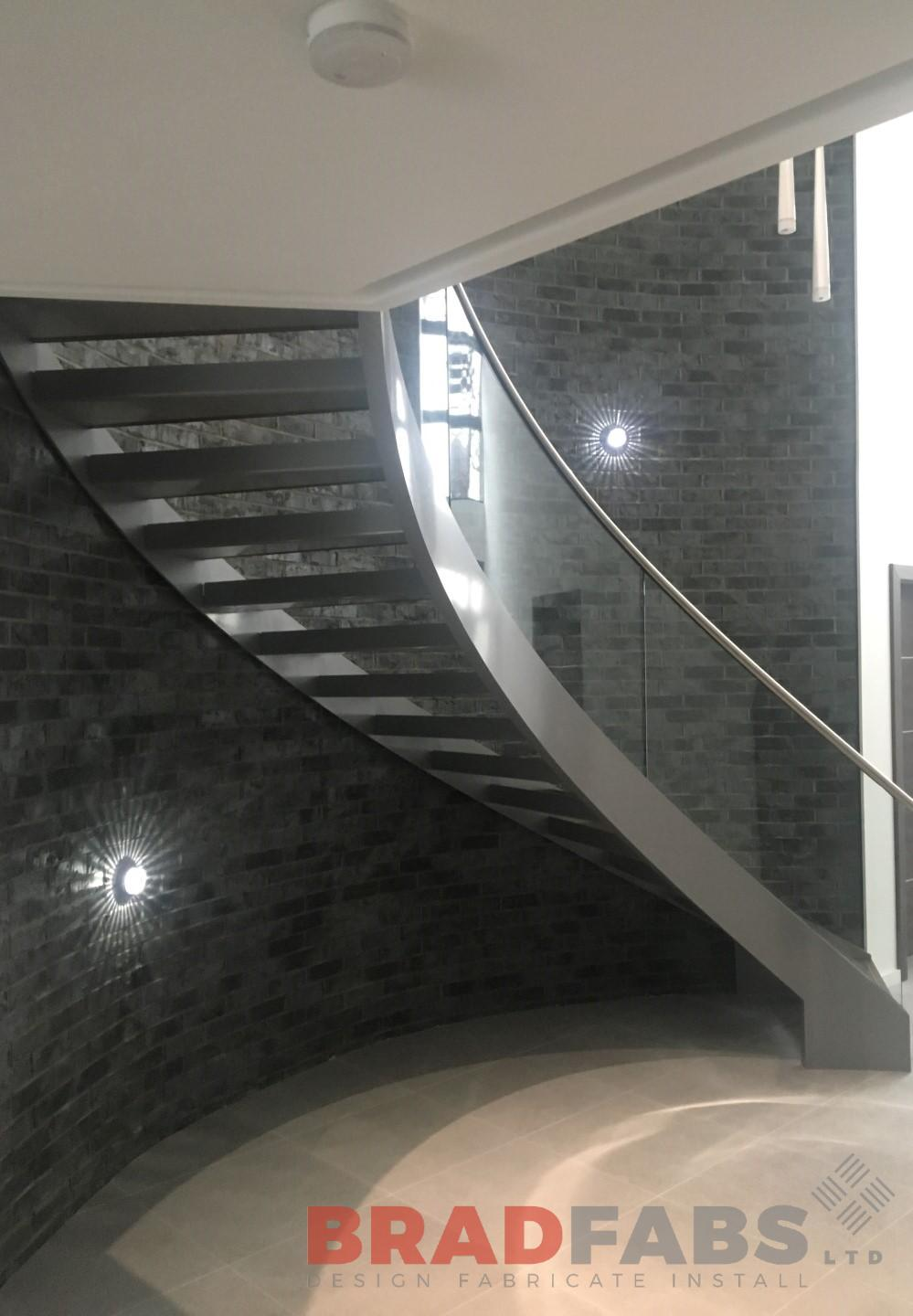 One off curved glass helix staircase designed, manufactured and installed by Bradfabs