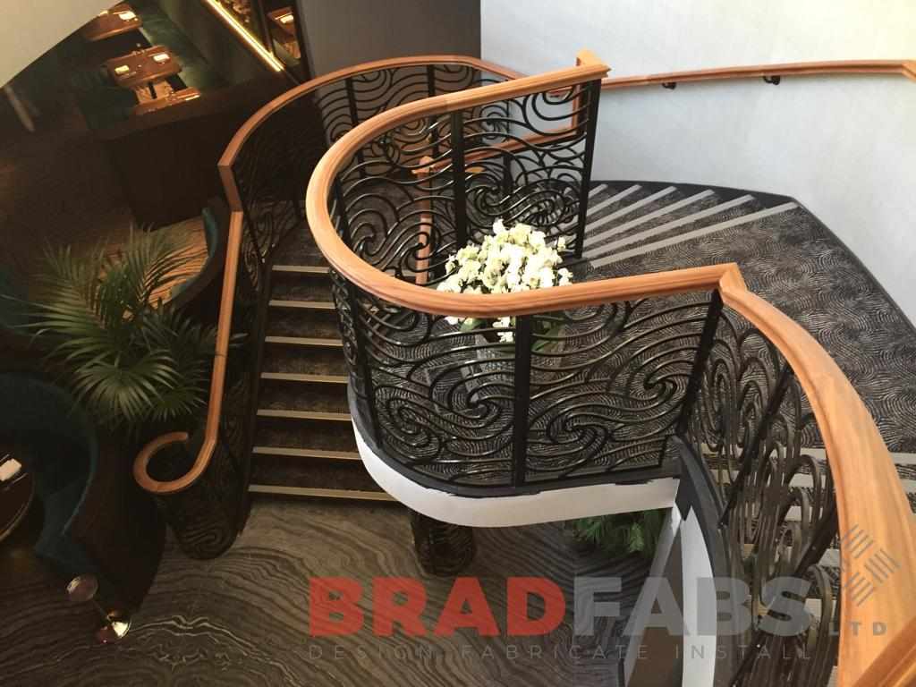 Stunning helical staircase with mild steel and powder coated black decorative balustrade and timber handrails by Bradfabs