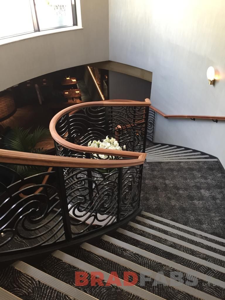 Timber handrails for this large helix staircase are wall mounted at one side, and at the other side the timber handrail is on top of some mild steel, powder coated black decorative balustrade by Bradfabs