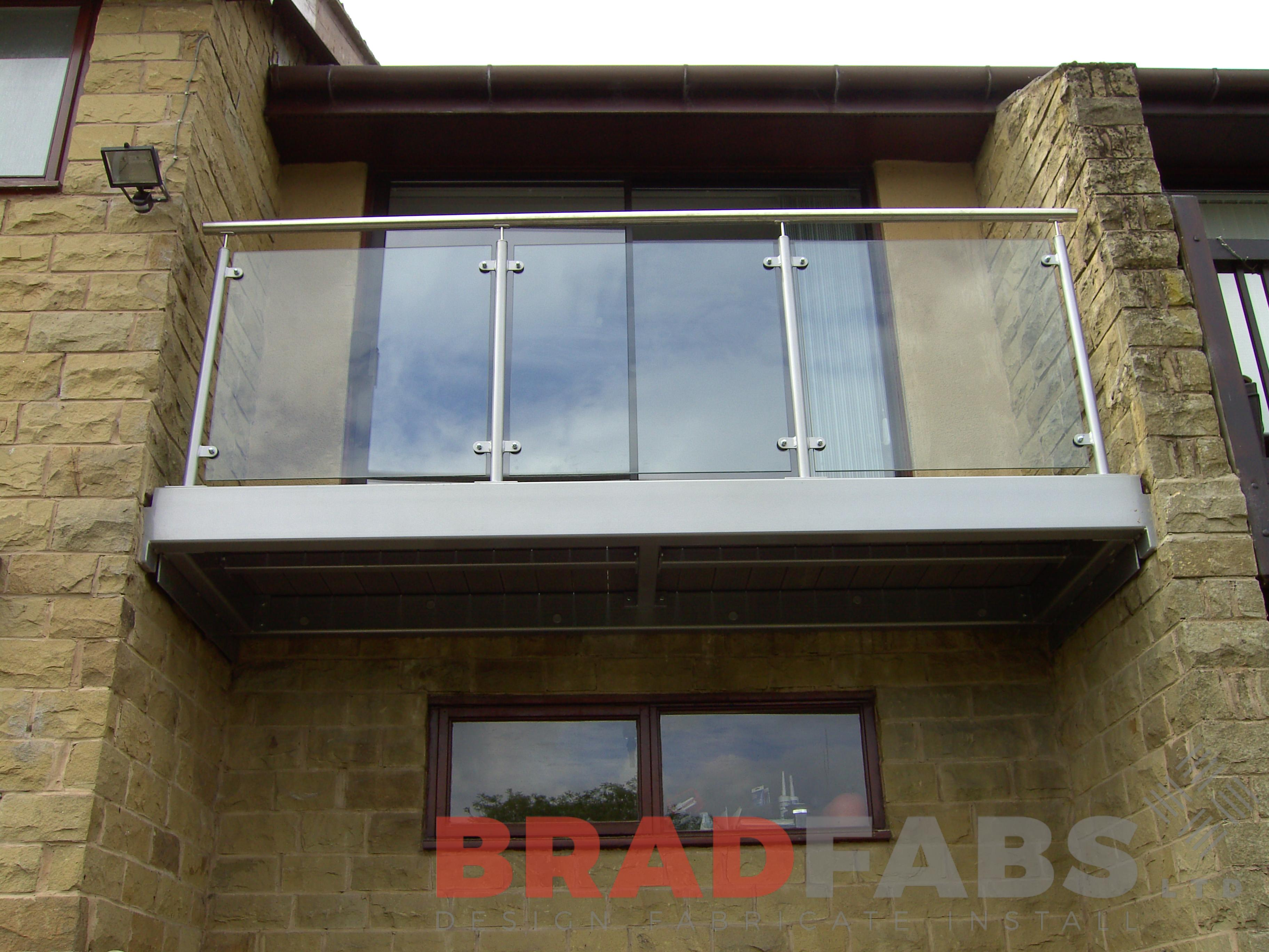 Small balcony outside a juliette window, manufactured in mild steel and galvanised. With glass infill panels and stainless steel balustrade complete with composite decked flooring by Bradfabs