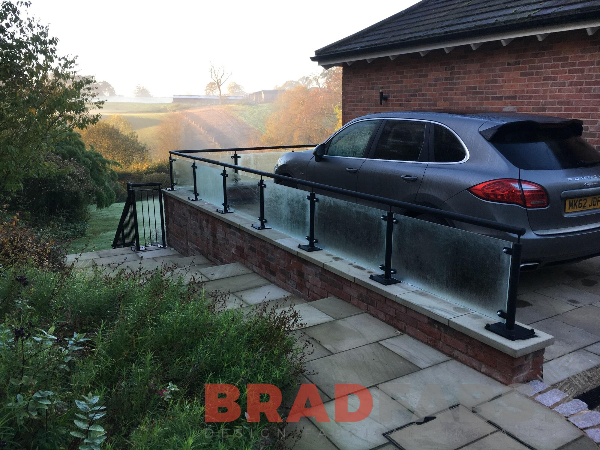 The top of our customers garden shows the mild steel, galvanised and powder coated black top rail with glass infill panels leading to the vertical bar balustrade down the stone steps leading to the garden by Bradfabs