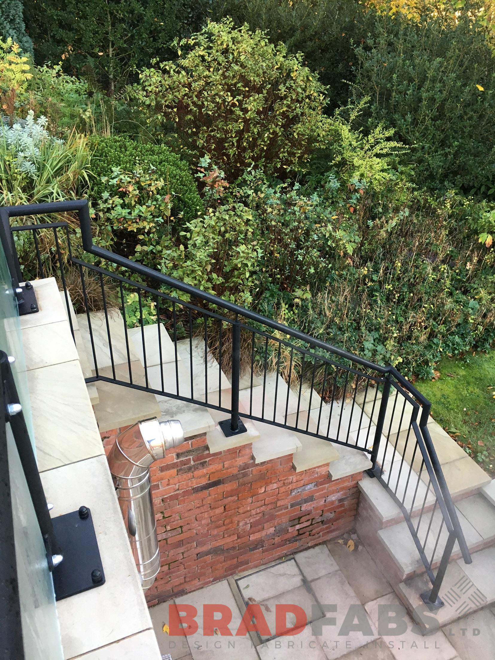 Mild steel, galvanised and powder coated black vertical bar railings going down the customers stairs to lead to their garden by Bradfabs