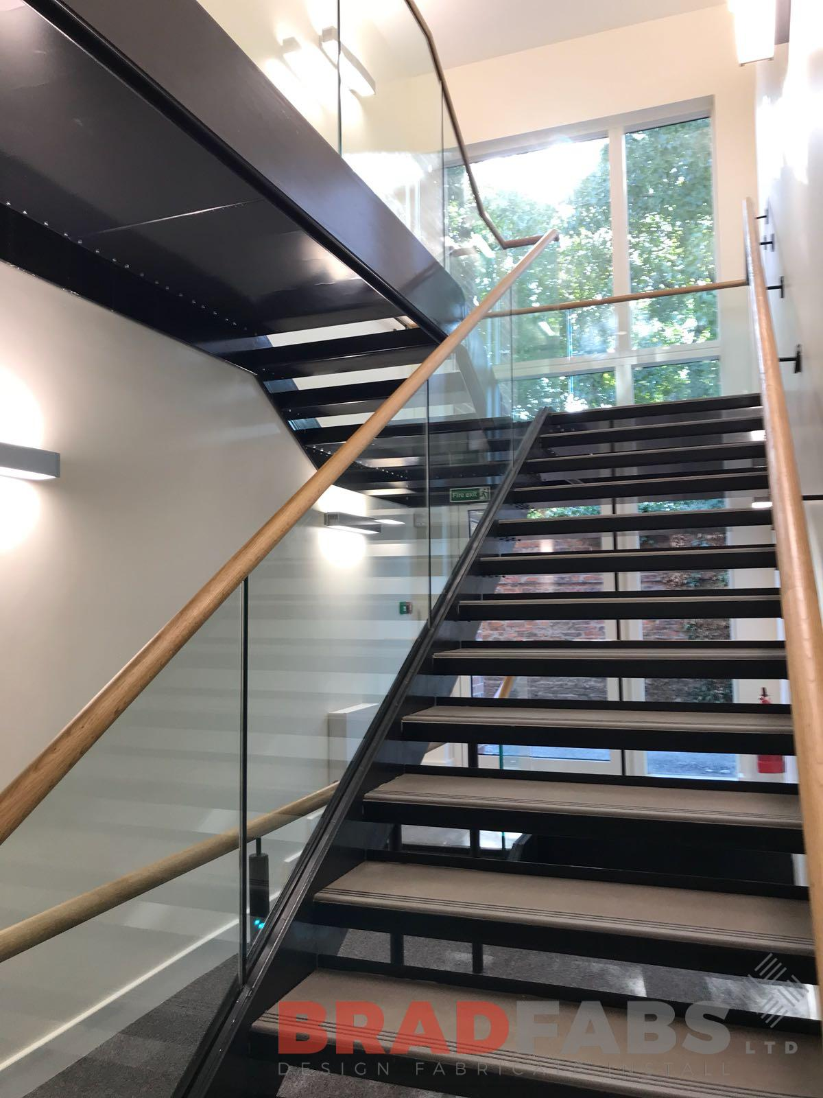 Wooden handrail, open treads, infinity glass balustrade, straight staircase