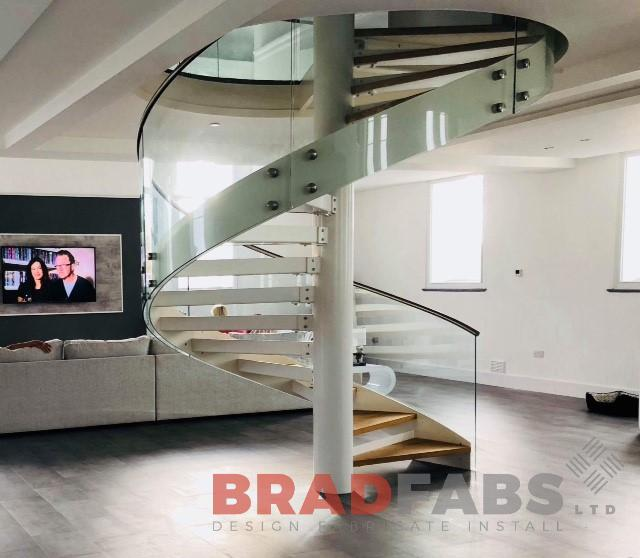 Spiral Staircase with curved face fixed glass with stainless steel top rail by Bradfabs
