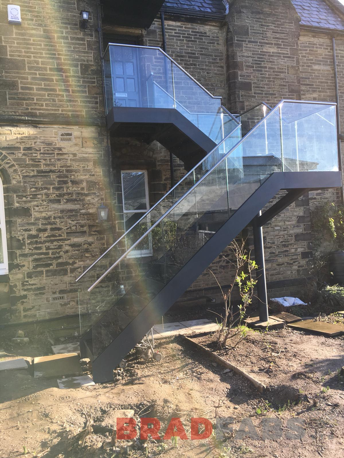 beautiful bespoke external straight staircase for a residential property, manufactured in mild steel, galvanised and powder coated with infinity glass balustrade and stainless steel handrail, with composite decked flooring by Bradfabs Ltd