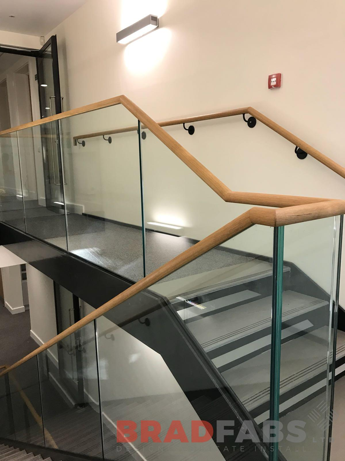 School staircase with glass balustrade and wooden handrail installed by UK based comany Bradfabs