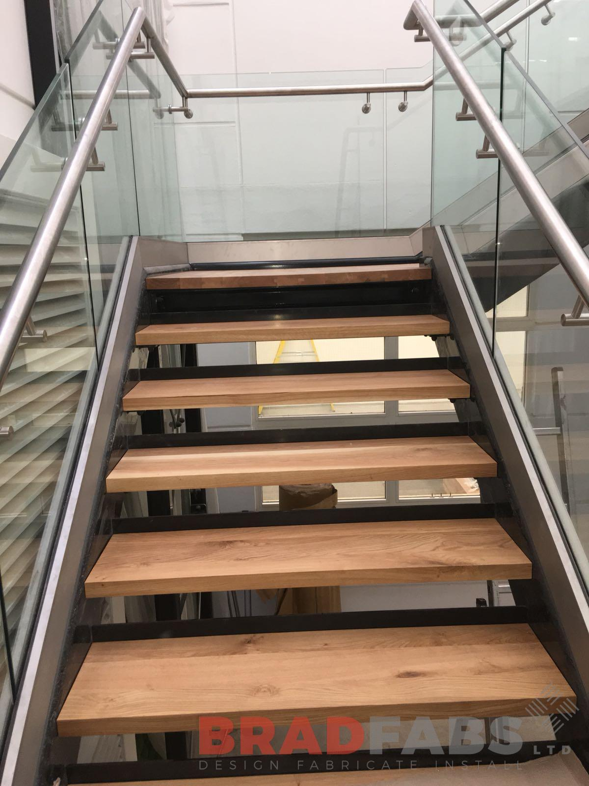 Commercial staircase with infinity glass balustrade and stainless steel handrail