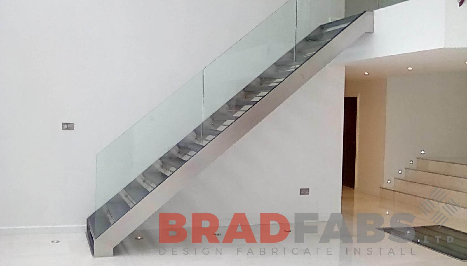 beautiful modern straight staircase in stainless steel with open treads and infinity glass balustrade by Bradfabs