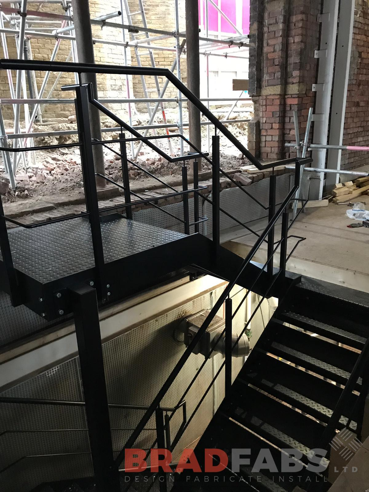 Mild steel, powder coated black straight staircase in a commercial property with durbar treads by Bradfabs
