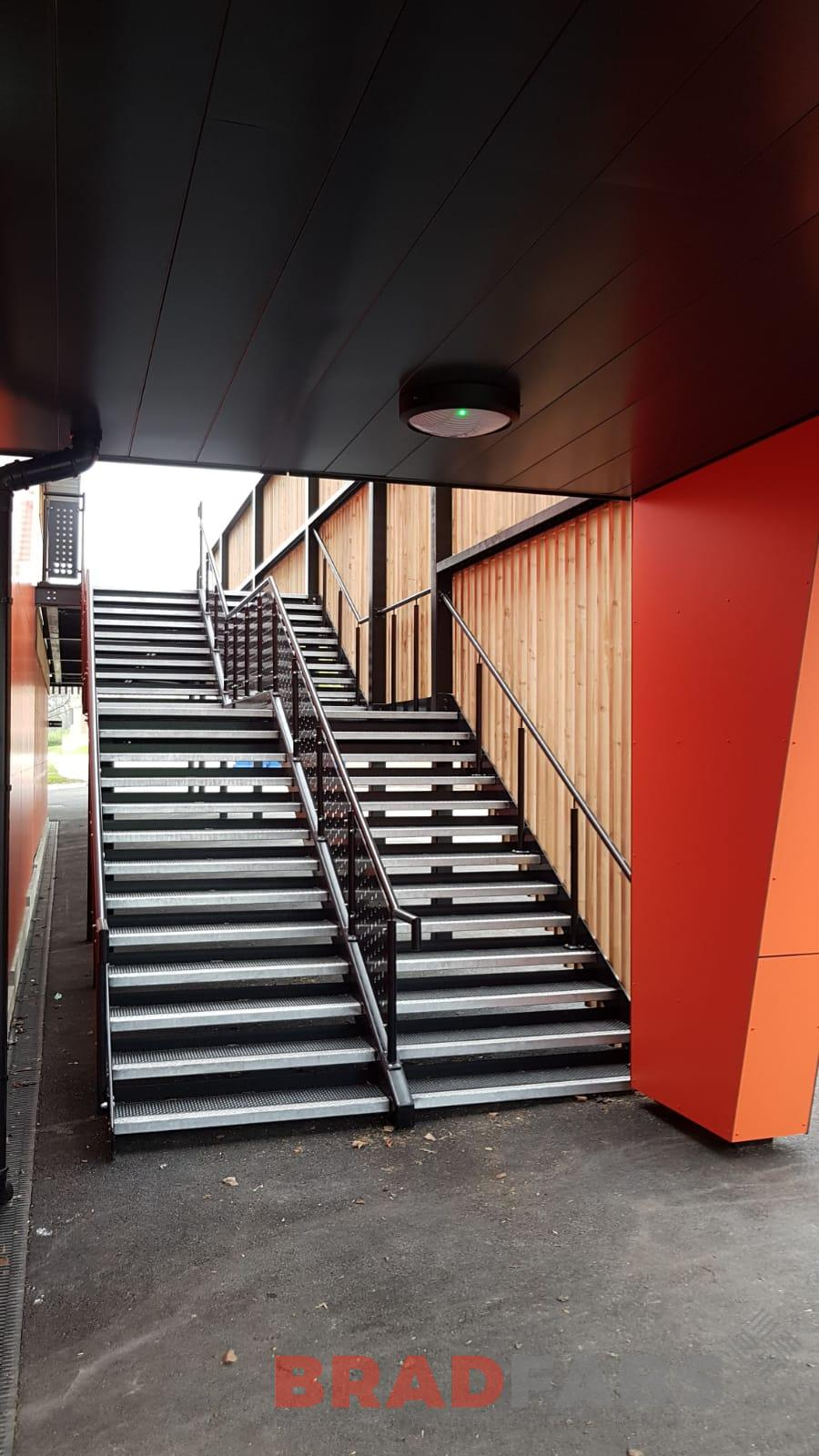 Large double straight staircase for a Grammar school, manufactured in mild steel, galvanised and powder coated black with decorative balustrade and BNOP5 (Octopus flooring planks) by Bradfabs