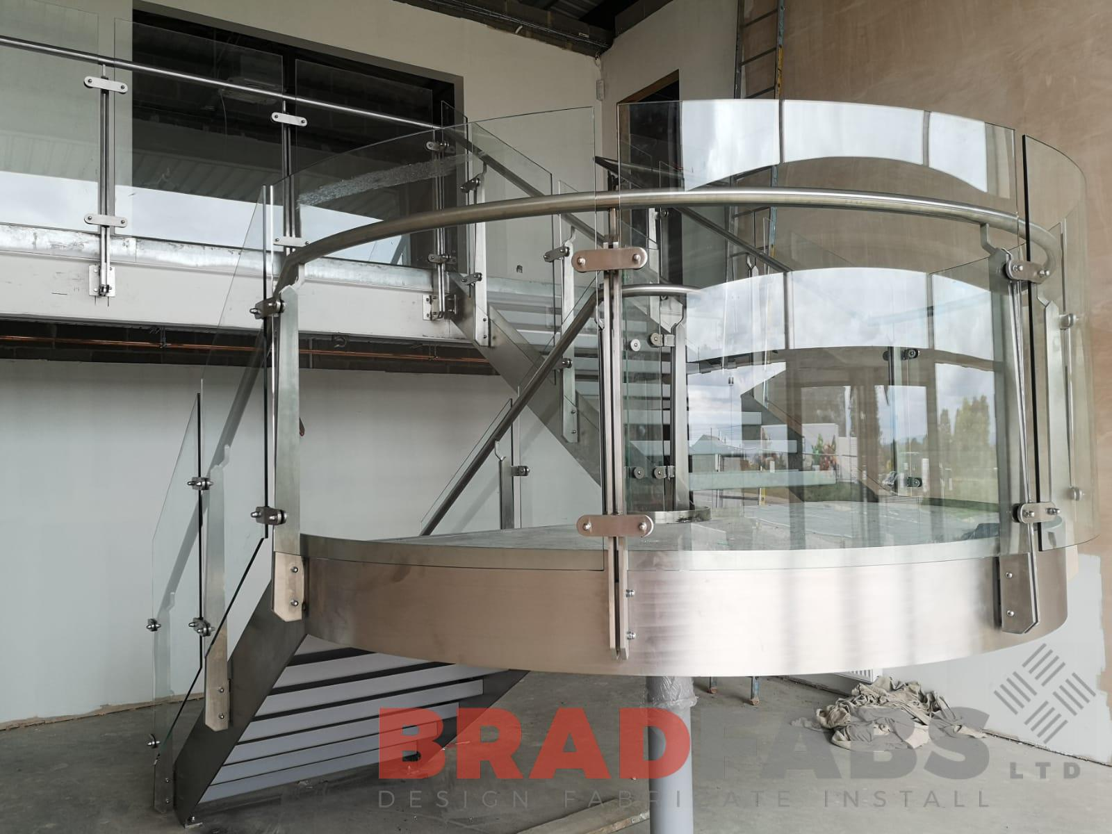Bespoke Stainless steel curved staircase frame with infinity glass balustrade by Bradfabs