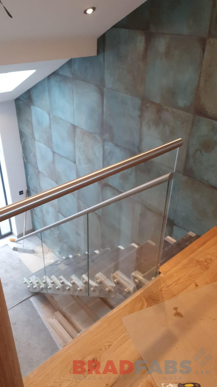 mild steel staircase with hidden stringer, oak treads and face fixed glass with stainless steel handrail by Bradfabs Ltd