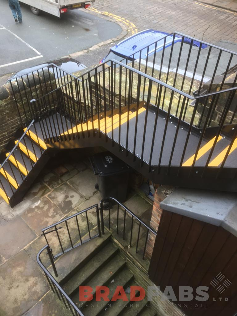 mild steel, galvanised and powder coated straight external staircase, with vertical bar balustrade on the stairs and landing, with durbar treads and yellow nosing by Bradfabs Ltd
