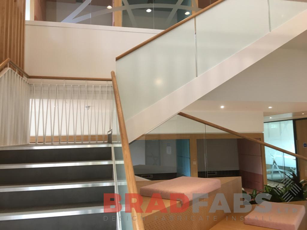 Large bespoke staircase for a commercial property by Bradfabs, decorative balustrade to one side and frosted glass balustrade to the other side, with timber handrail