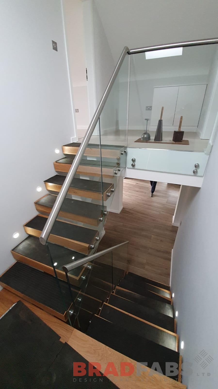 single spine straight staircase for a domestic property, with stainless steel top rail and infinity glass balustrade, complete with oak treads by Bradfabs