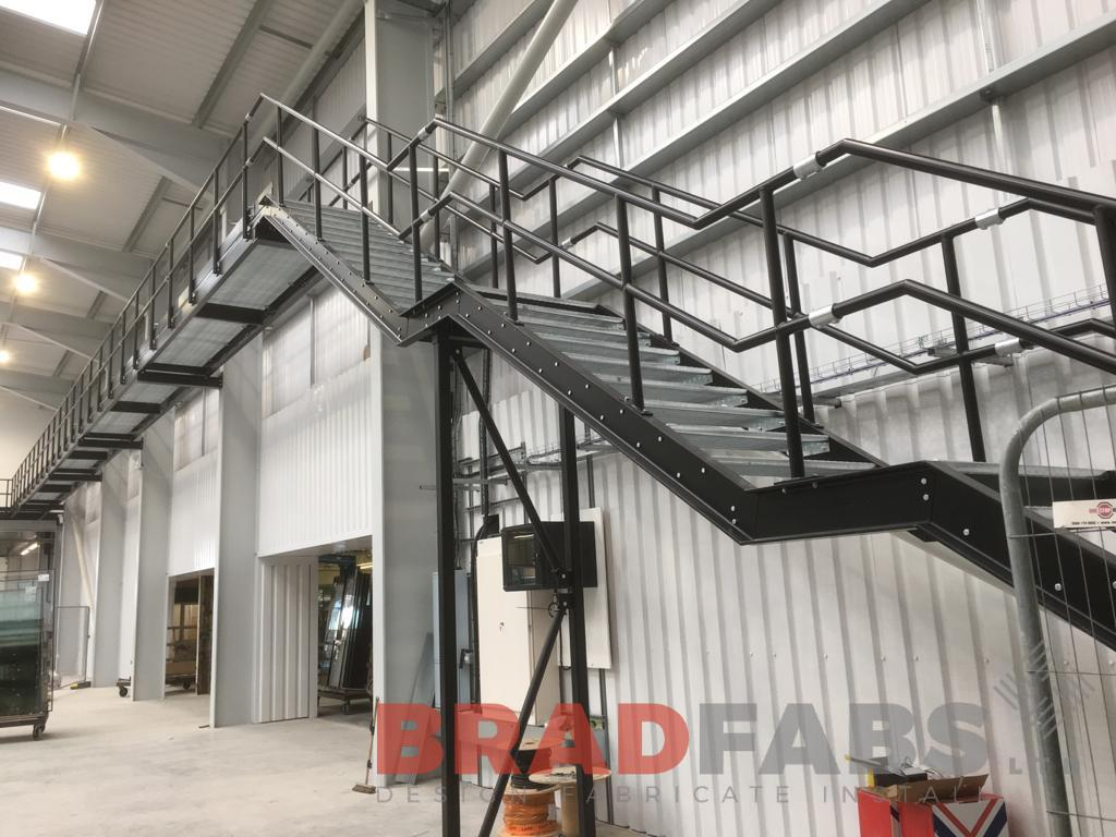 large bespoke steel internal staircase leading to a large walkway, for a workplace project by Bradfabs