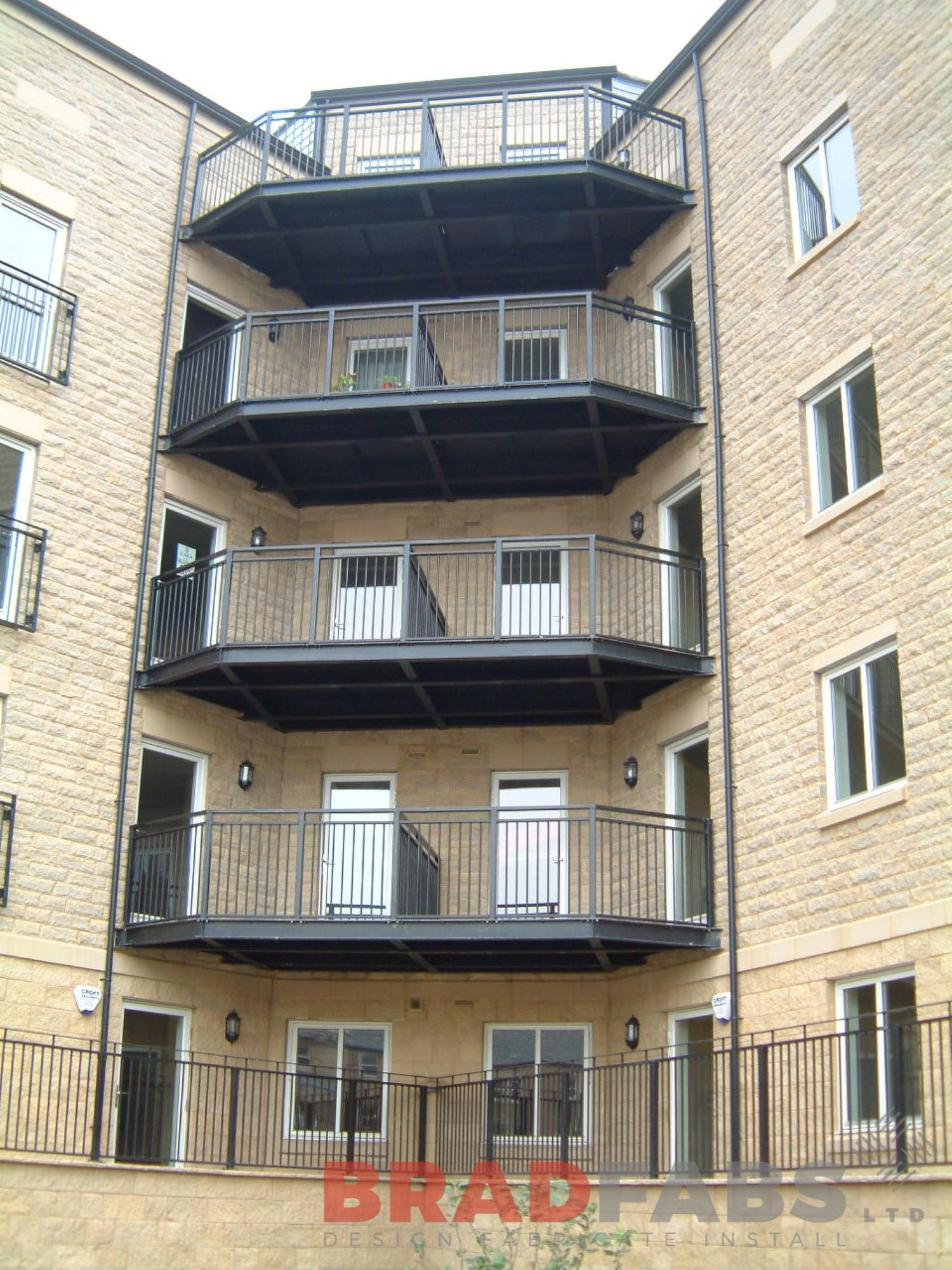 Set of four large balconies on a block of new flats, all manufactured in mild steel, galvanised and powder coated black with vertical bar balustrade and complete with composite decked flooring by Bradfabs